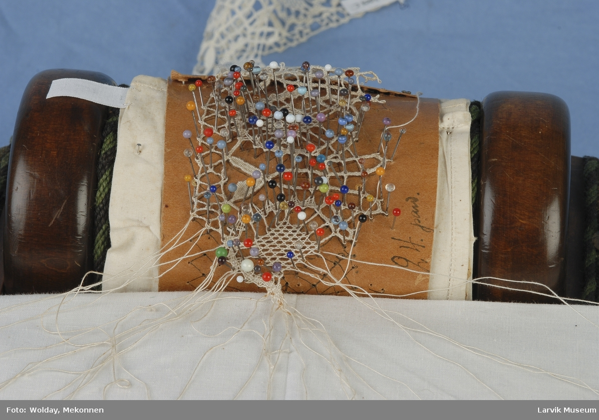 Form: rund underplate av bjerk,oval overplate av  mahogny, m oppstikkende valse,sidedelene polstret og trukket m grønn ullrips,to messingknotter og to do. øyen- skruer,1 1 1/2 par pinner m tråder forbundet til valsen hvor påbegynt knipling i lin i Chr. IV-mønster,11 rapporter full- ført,masse knappenåler m glasshoder i prikkebrevet