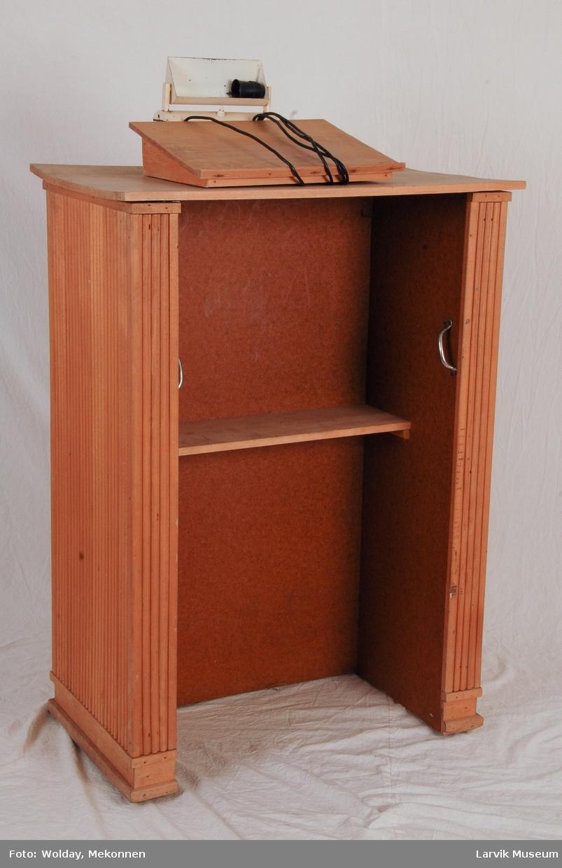Form: Et høyt bord med tre hele sider som ben. En løs skrå del som står på den med en fastmontert lampe.
