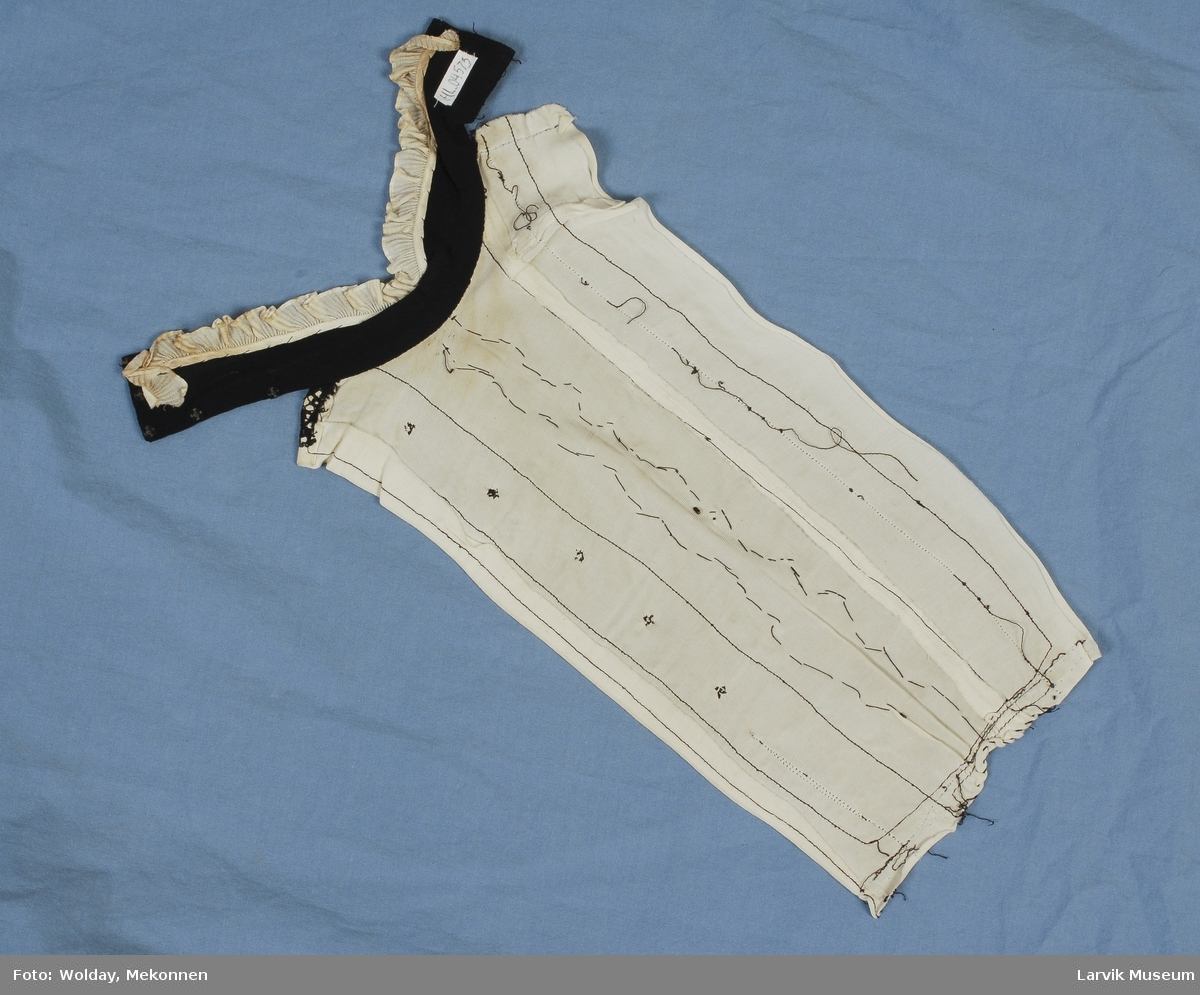 Form: To loddrette blonder sydd på en sort krage, med hvit rysjekant. Festet i halsen med trykknapper. Det sitter dessuten igjen den ene delen av trykknapper nedover den ene blonden.