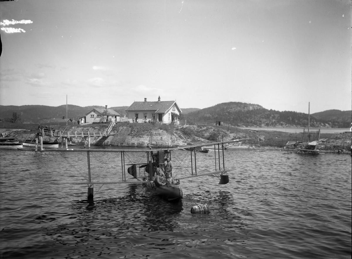 Flybåt med piloter ombord fotografert. Ant. fotografert i Eidangerfjorden ved Dalen i 1922. Flytype Supermarine Channel, F.38 tilhørende Marinens Flyvevesen. Bildet viser en flybåt av typen Nielsen & Winther F.a., som Einar J. Juell kjøpte i Danmark i mars 1919 og fikk levert i august. Han fløy det over til Norge og det skulle registreres som N.1, den aller første registreringen i Norge. Ble derimot aldri registrert. Flybåten F.38 (1) havarerte 12. juli 1920 i Kristiania (Oslo), men Marinens flyvåpen tok over en sivil Supermarine Channel i april 1921, og det ble i mai 1922 pånytt registrert som F.38 (2), d.v.s. den andre med F.38. Det fløy fram til 1. mars 1928 i alt 107 timer og 52 minutter for Marinens flyvåpen. Dette var et fly av Det Norske Luftfartrederi, og fløy da som N.11 på ruten Stavanger-Haugesund-Bergen. Den 23. september 1920 falt motoren fra rammen og ødela skroget. Piloten, Fredrik Lie Vogt, klarte å komme ned, men flyet ble fraktet til Horten for reparasjon. Dit ankom det i november 1920.