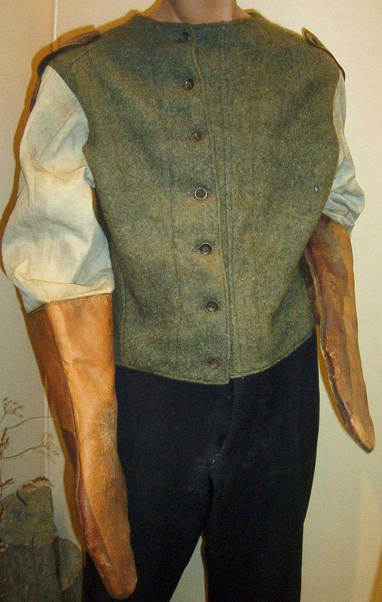 Enkel trøye i vadmel og lerret med lærhansker som er sydd fast til ermene, noe som gjør den til en form for tvangstrøye. Trøya har skulderklaffer i lær og sju metallknapper i front.