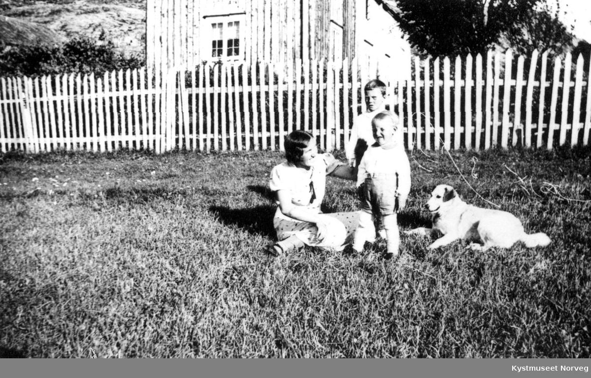 Ukjente - kvinne med to barn og hund i gresset