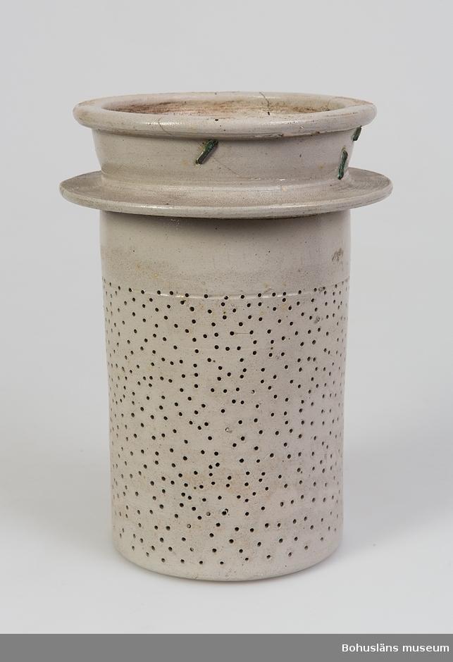 """Kärl för förvaring av blodiglar.  Ur handskrivna katalogen 1957-1958: Kärl av lergods f. blodiglar. I 3 delar a-c. a) h. 23,5; D. 19 cm;  runt om dubbel pärlstav av ranka av 4-klöver;  """"Hirudines"""" i blått;  2 runda fästen f. handtag. b) Insats i form av sil; H. 23, D. (upptill) 15 cm. Trasig, lagad  m. mässingstenar. c) Lock över insatsen; D. 11 cm; välvt, vid sidan av ett litet handtag. Helt.  Lappkatalog: 94"""