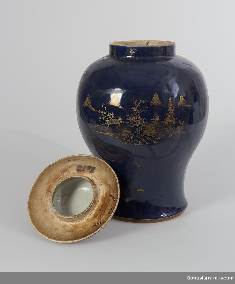 Ur handskrivna katalogen 1957-1958: Kinesisk urna, blå m. lackering Bottendiam. c:a 18. H. (med lock:) c:a 43,5. Porslin, blå med guldmönster. Lagad.  Lockurna i monokrom mörkblå glasyr; förgylld teckning av landskap/öar, pagoder, träd, berg m.m. Stora delar av dekoren avnött. Den mörkblå ytan består av pudrat blått eller pulverblått (powder blue), en i Kina vid 1600-talets slut lanserad koboltblå fondfärg för keramik, vilken blåstes över föremålen genom ett med tunt tyg överdraget bamburör.  På ytan kunde man antingen spara ut mönster som sedan fylldes med dekor i andra färger, eller som i detta fall täcka ytan helt. Den bildar i sin tur efter bränning underlag för ett guldmåleri med landskaps och figurscener. Tekniken kopierades i Sverige på 1740-talet av bl.a. Rörstrand.