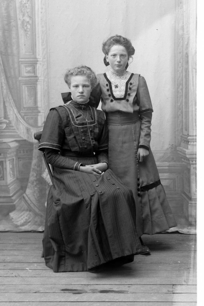 Studioportrett av to kvinner.