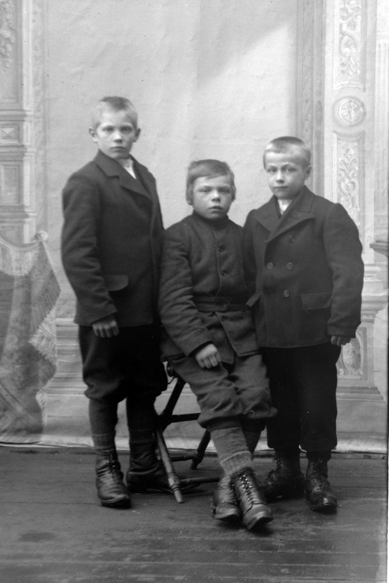 Studioportrett i helfigur av tre unge gutter.