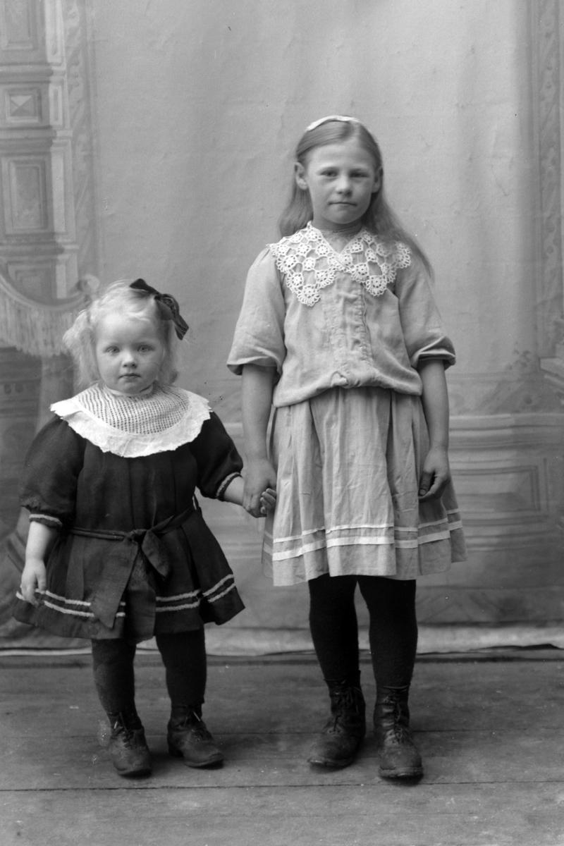 Studioportrett av to unge jenter som holder hender, trolig søstre.