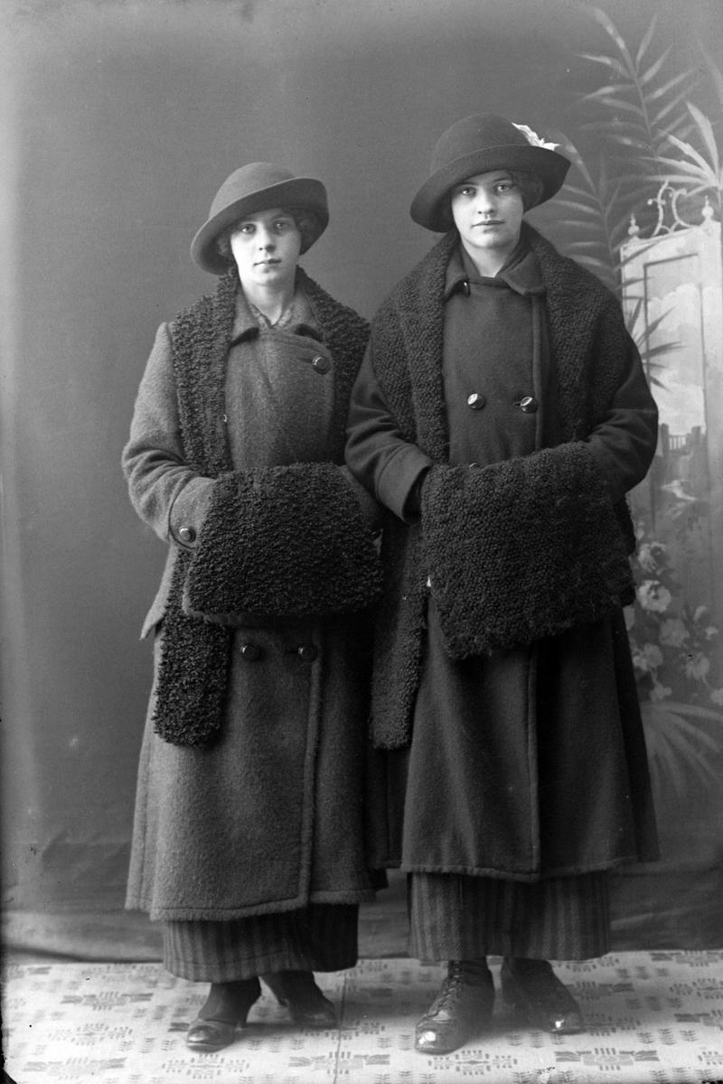 Studioportrett av to kvinner med to hatter og muffer.