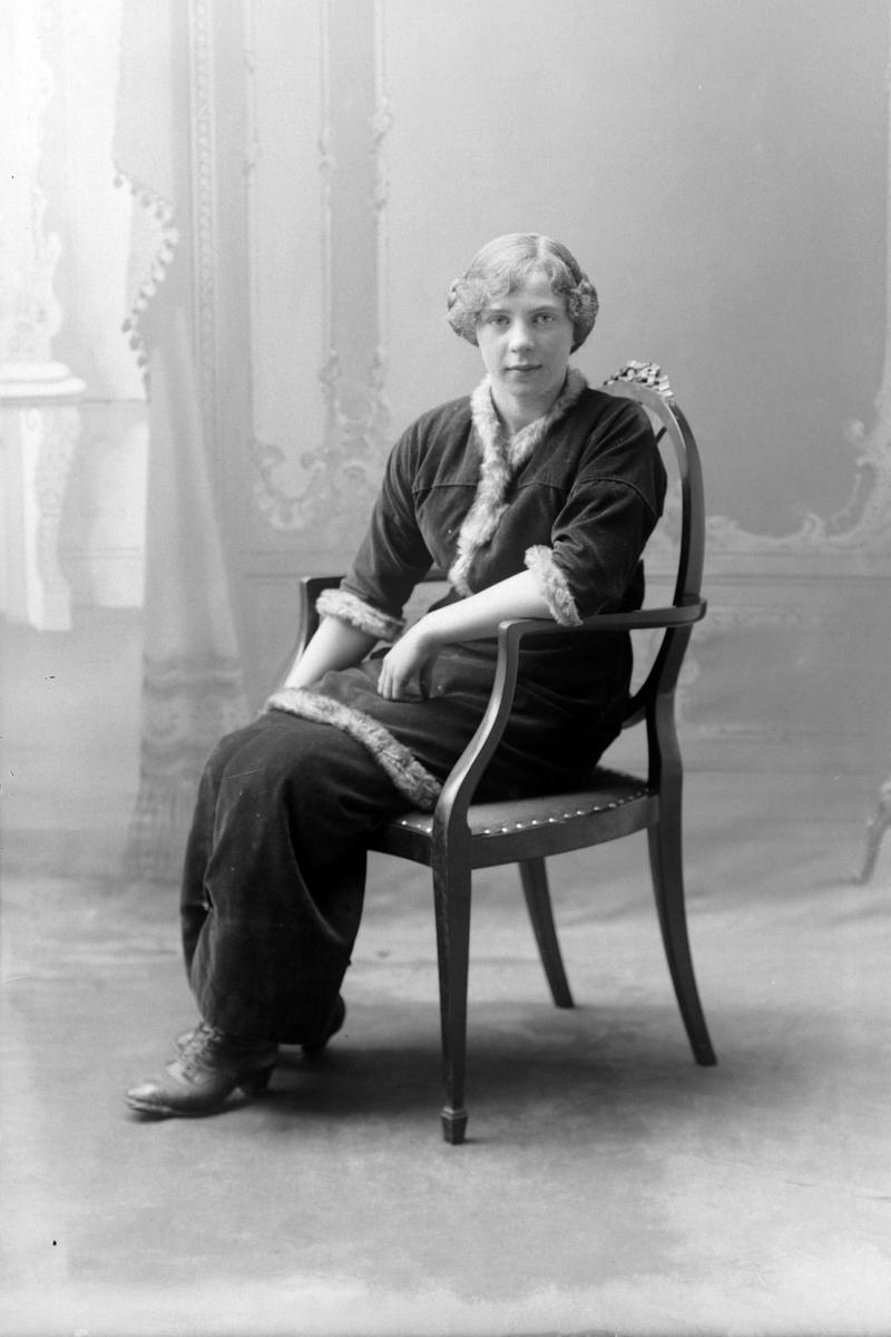 Studioportrett av en kvinne som sitter i en stol.