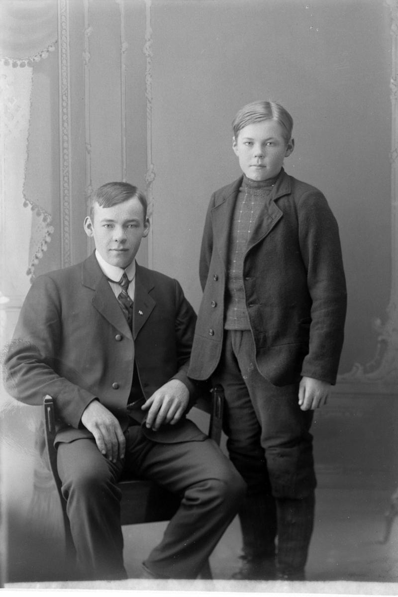 Studioportrett av ung mann ved siden av en gutt.