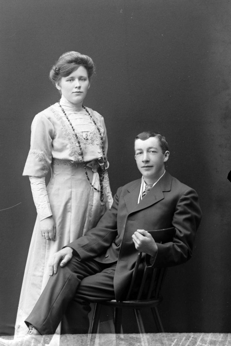 Studioportrett av en kvinne som står ved siden av en sittende mann.