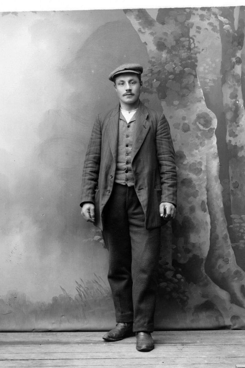 Studioportrett av en mann med sixpence.