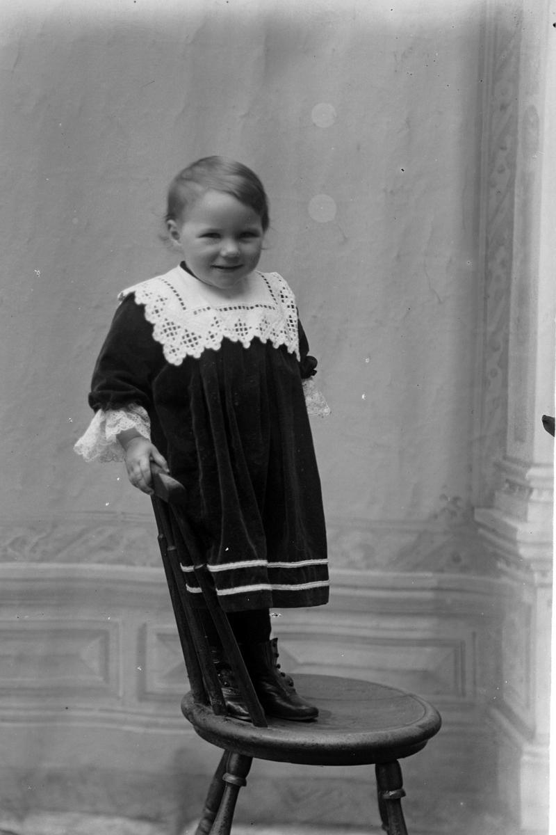 Studioportrett av et barn som står på en stol.