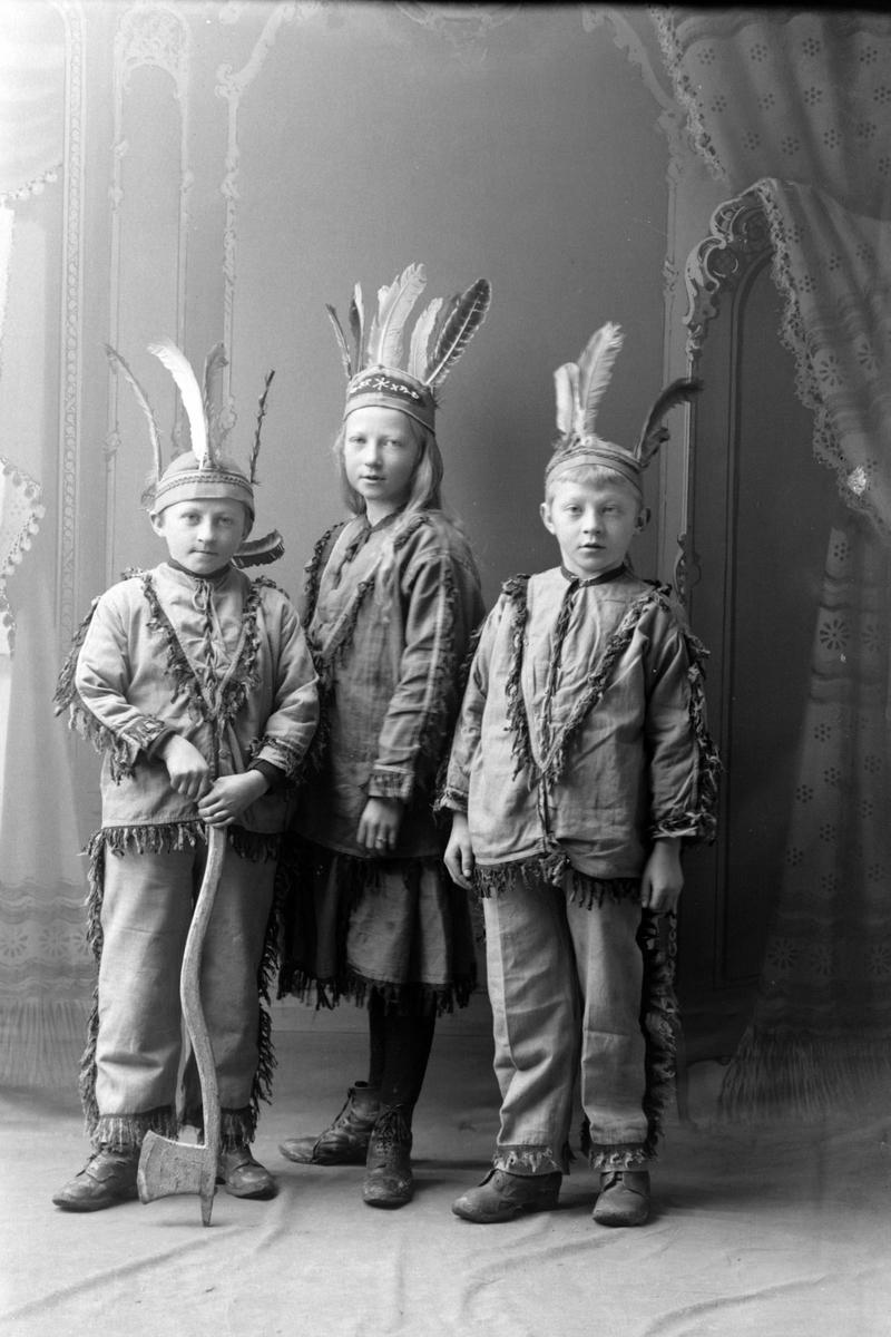 Studioportrett av tre barn utkledd som indianere.