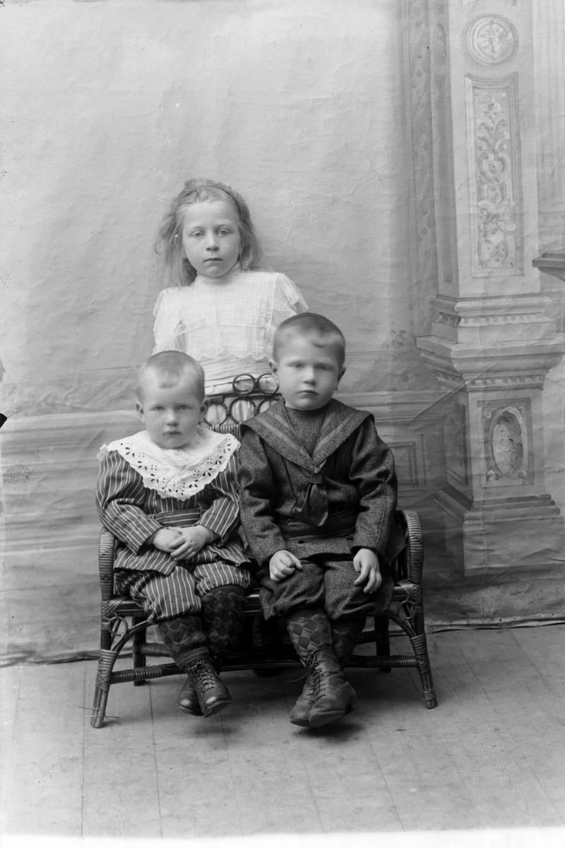 Studioportrett i helfigur av tre barn.