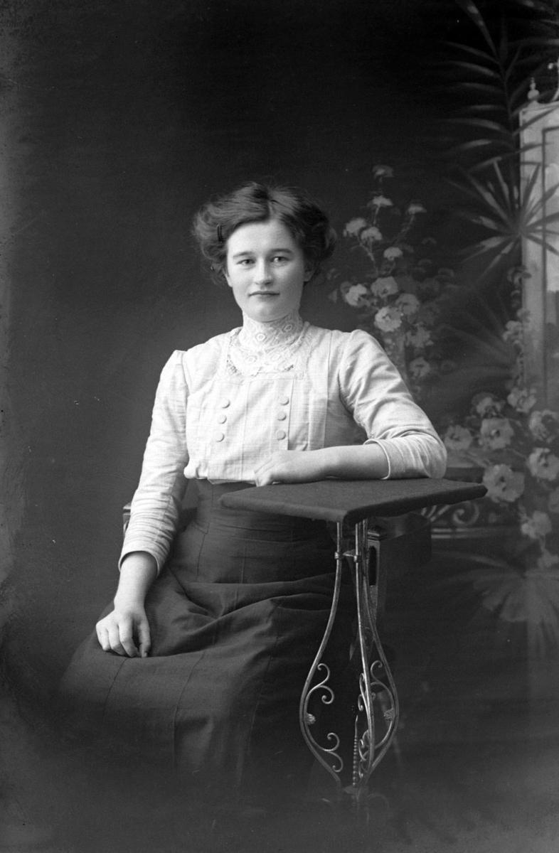 Studioportrett av en sittende kvinne.