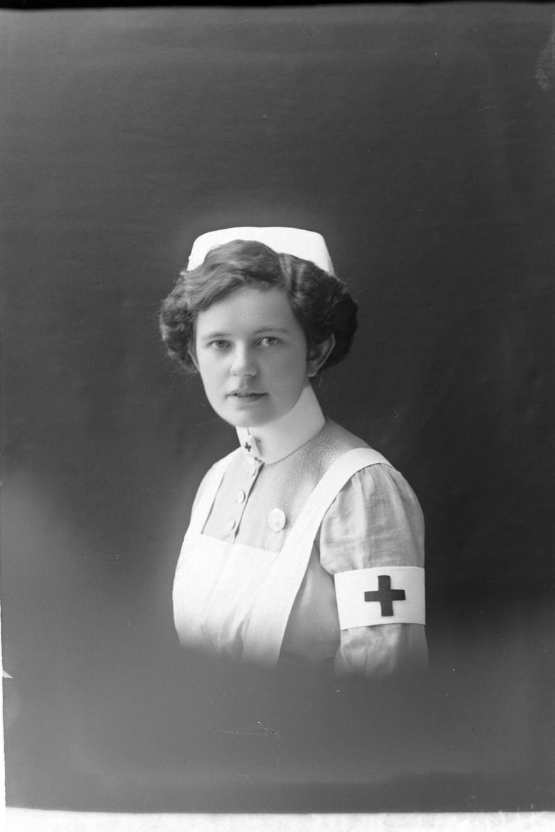 Studioportrett av en sykepleier i halvfigur.