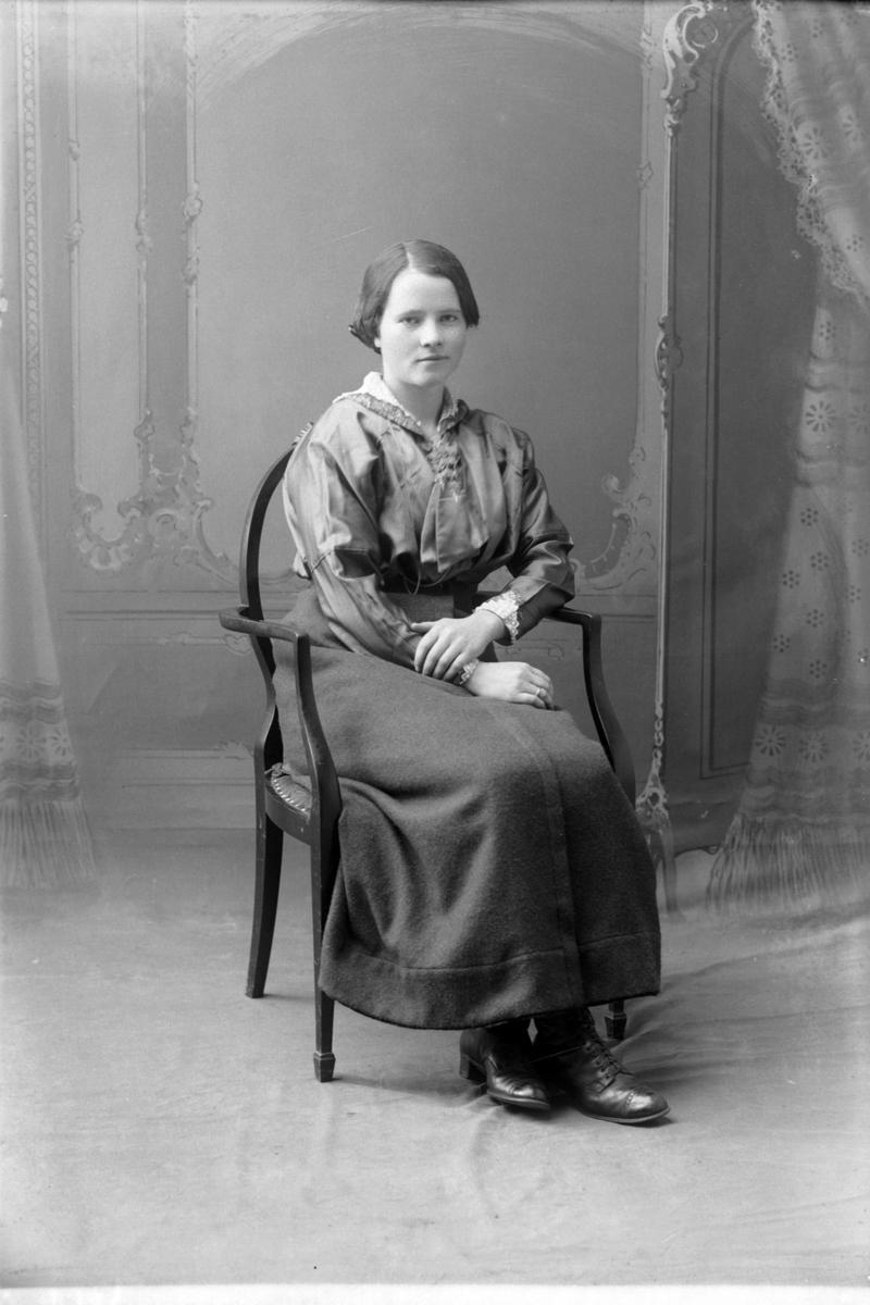Studioportrett i helfigur av en kvinne i en stol.