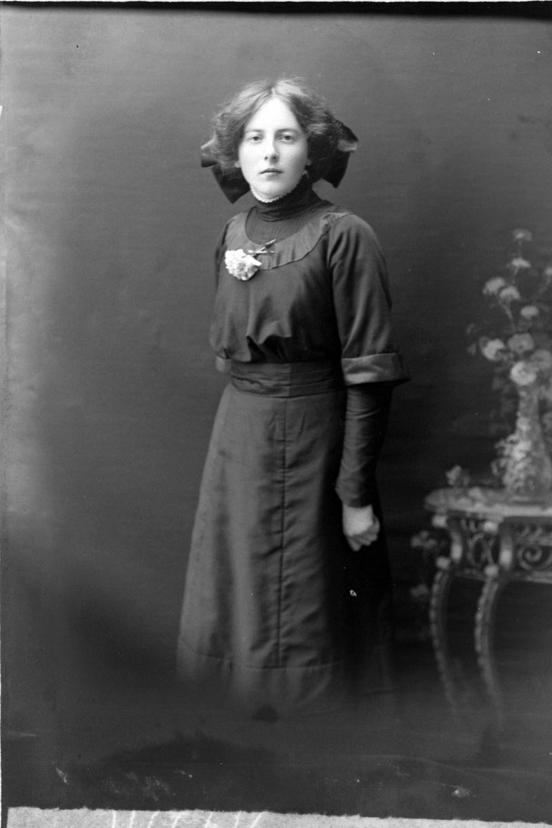 Studioportrett av en ung kvinne med sløyfe i håret.