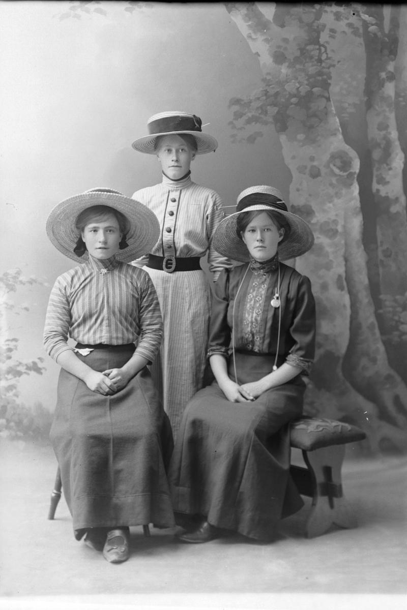 Studioportrett av to kvinner som sitter og én som står.