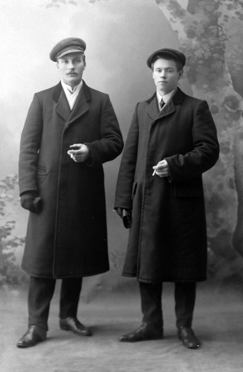 Studioportrett av to menn med frakker og luer.
