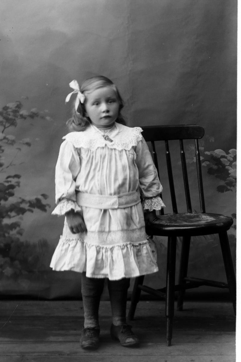 Studioportrett av en jente med sløyfe i håret.