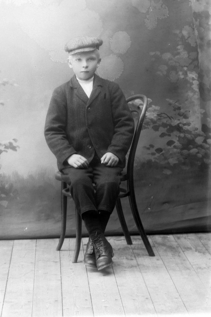 Studioportrett av en gutt som sitter på en stol.