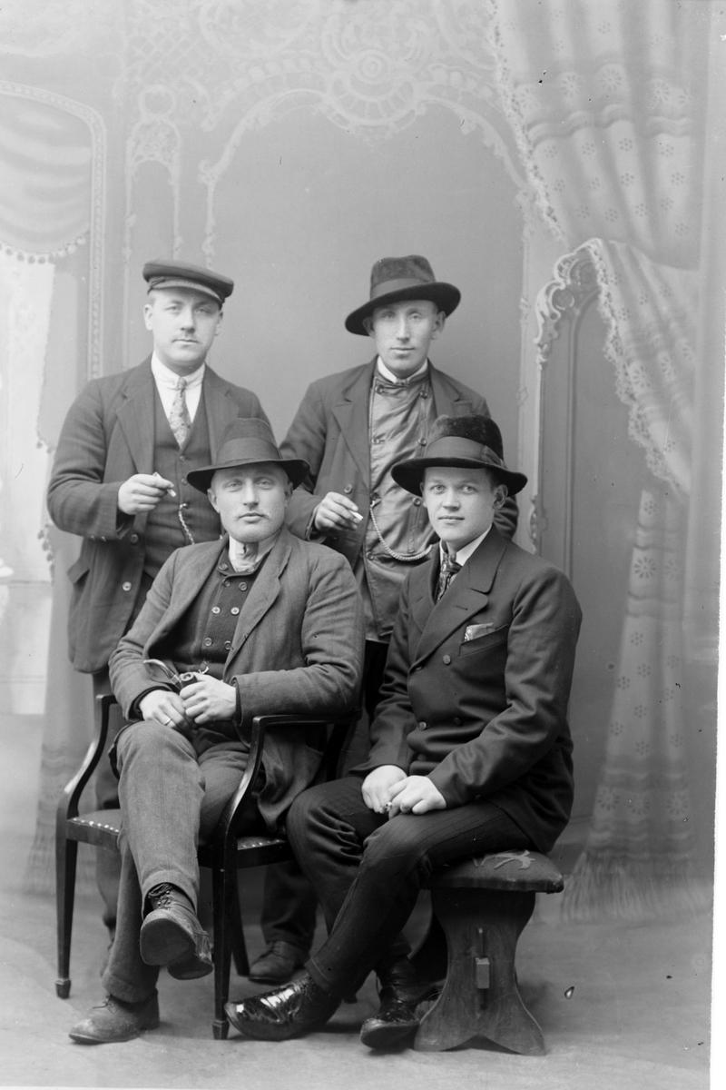 Studioportrett av fire menn.