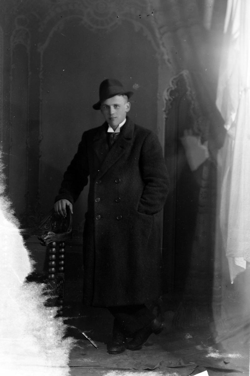 Studioportrett av en mann med en fedora eller trilby på hodet.