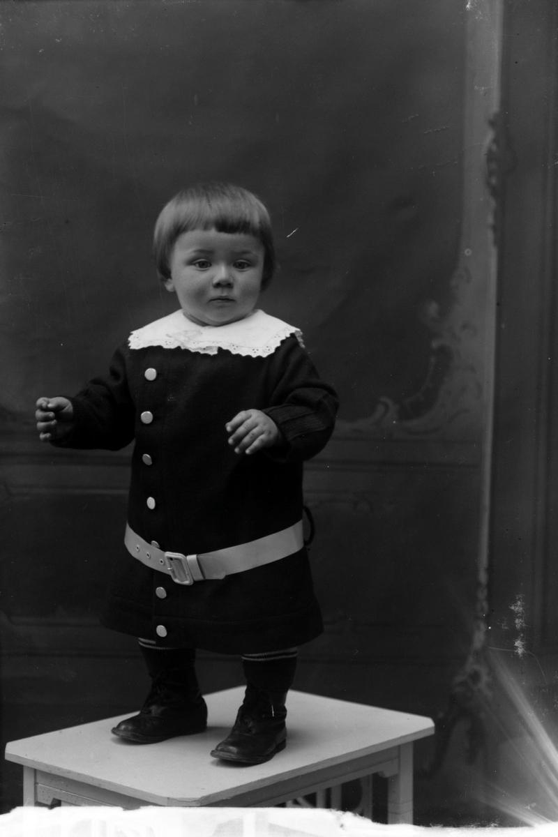 Studioportrett av et lite barn i helfigur.