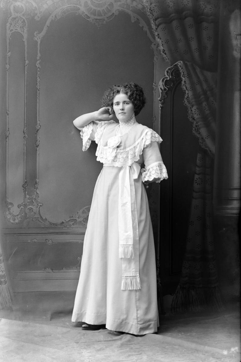 Studioportrett av en kvinne i en lys kjole.