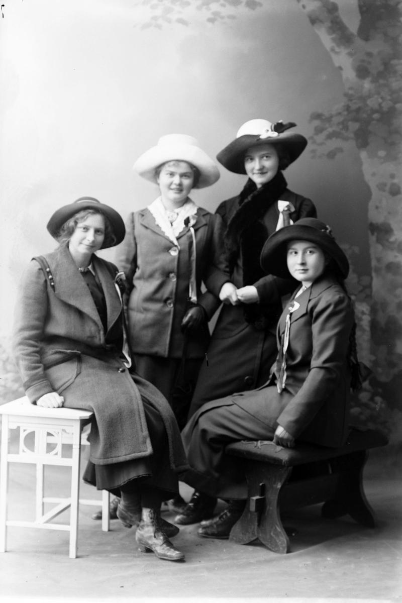 Studioportrett i helfigur av fire kvinner.