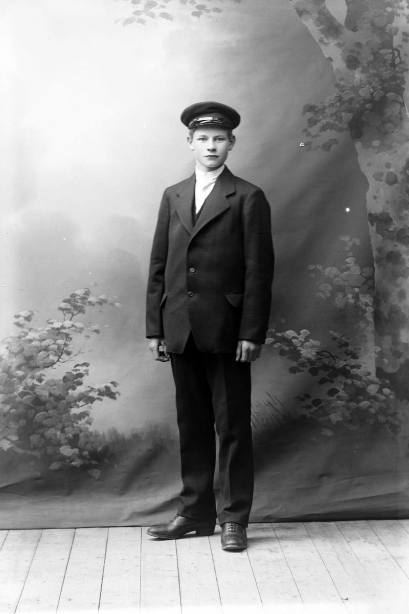 Studioportrett i helfigur av en ung mann.