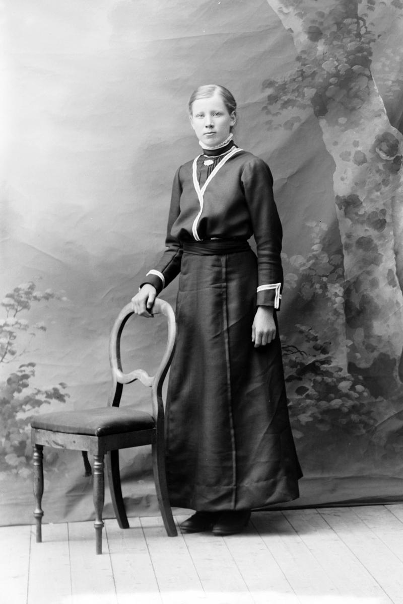 Studioportrett av en kvinne med hånden på en stolrygg.