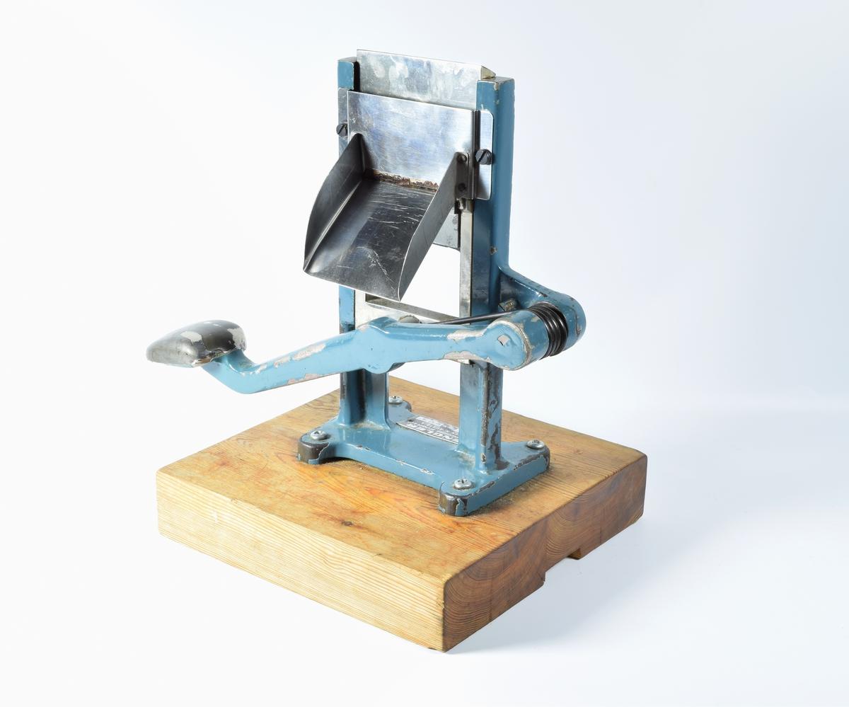 Maskin for å lukke enden av tuber etter at de er fylt med salve. Maskinen fungerer ved at en stående, tykk metallplate presses ned på enden av metalltuben slik av den blir klemt mellom to plater. Den oppereres ved hjelp av en lang spak.  Maskinen er montert på en tykk sokkel av tre.