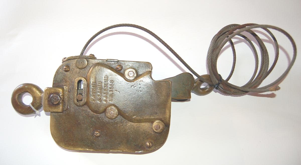 Formen er rektangulær med avrunda hjørner, med eit øye i kvar ende. Til låsen er det festet en utløsersnor av vaier.
