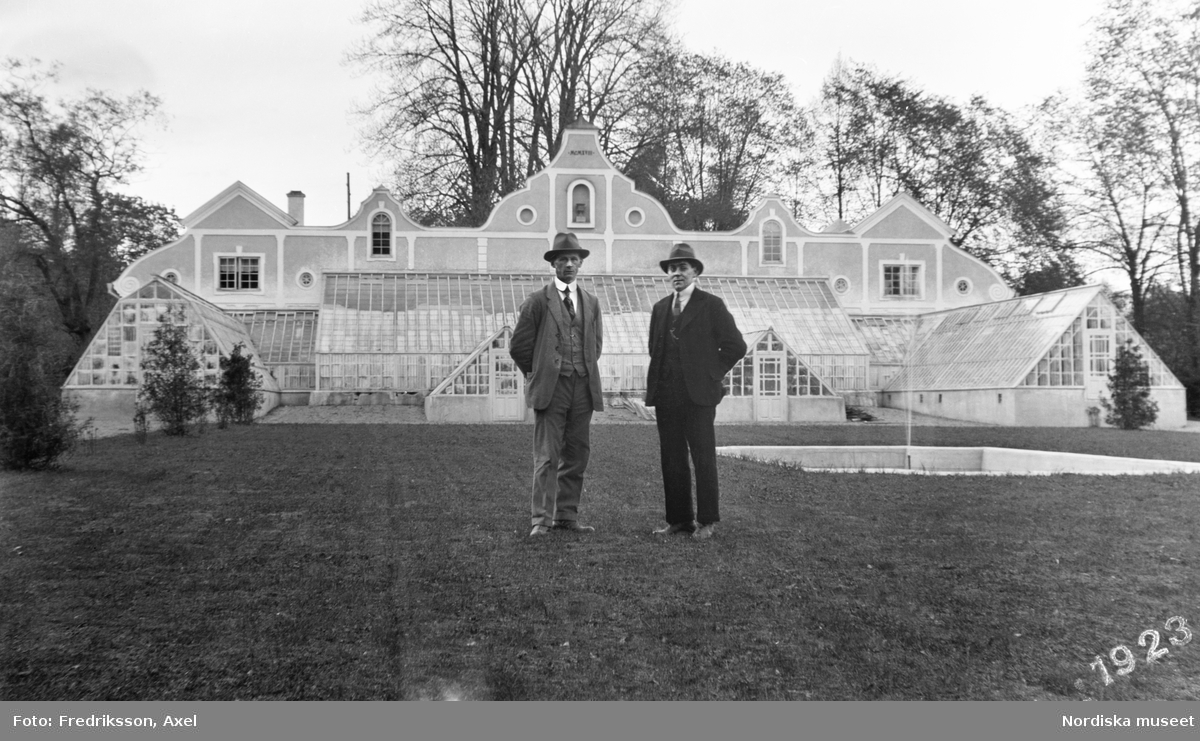 Två män i kostym och hatt står framför växthusen på Julita i Södermanland.