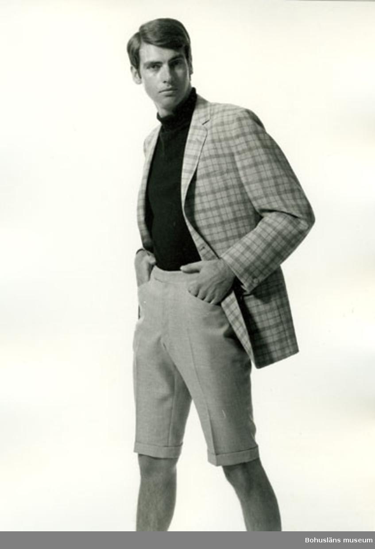Man i rutig kavaj och ljusgrå kortbyxa med slag samt svart polotröja. Kläder för fritid tillverkad av Schwartzman & Nordström (Tiger-fabriken), Uddevalla
