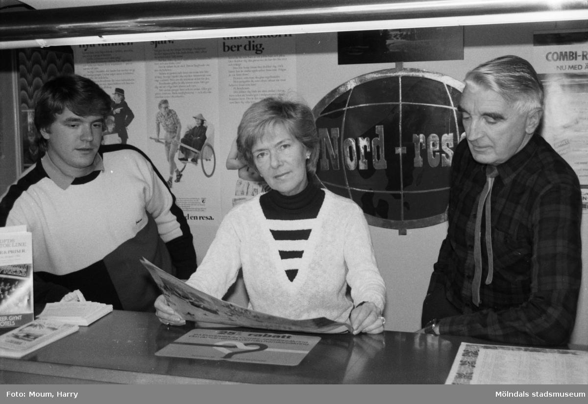 """Resebyrån Nord-Resor på Frälsegårdsgatan i Mölndal, år 1984. """"Familjen Ewlind, sonen Per-Anders, fru Maj-Britt och Carl-Ryno, planerar en resa.""""  För mer information om bilden se under tilläggsinformation."""