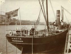 Dampskip med norsk flagg oppankret ved kai i fremmed havn. S