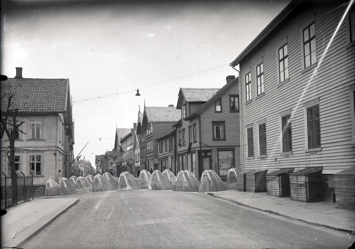 Veisperring med Hitlertenner i Strandgt. Huset til høyre er Haugesund trygdekasse (Strandgt. 99), med kasser spikret foran kjellervinduene. Fotografert fra sør mot nord.