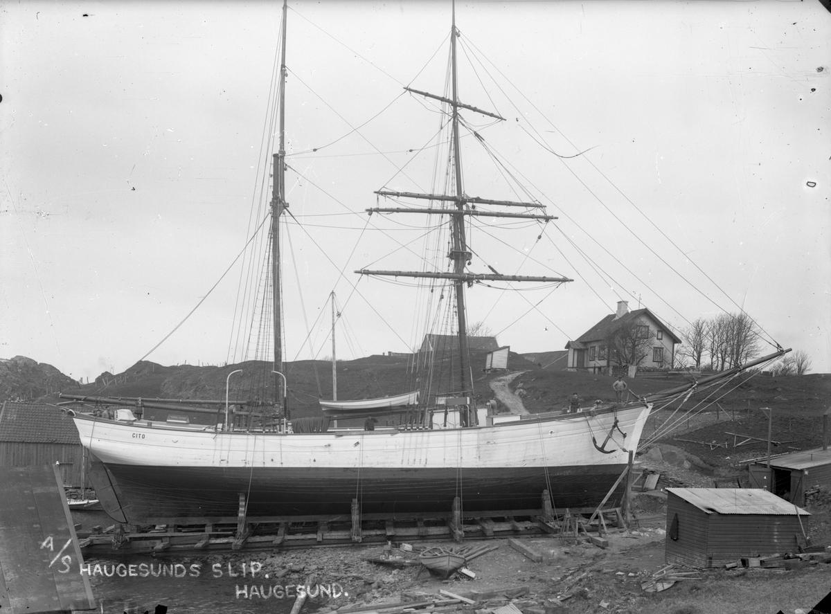 """Galeasen """"Cito"""" på land på """"Haugesunds slip"""", sørvest på Risøy. Fire mann står ombord. Det er naust på begge sider av slippen og et båtopptrekk til nærmest i bildet. På åsen i bakgrunne står det to hus."""