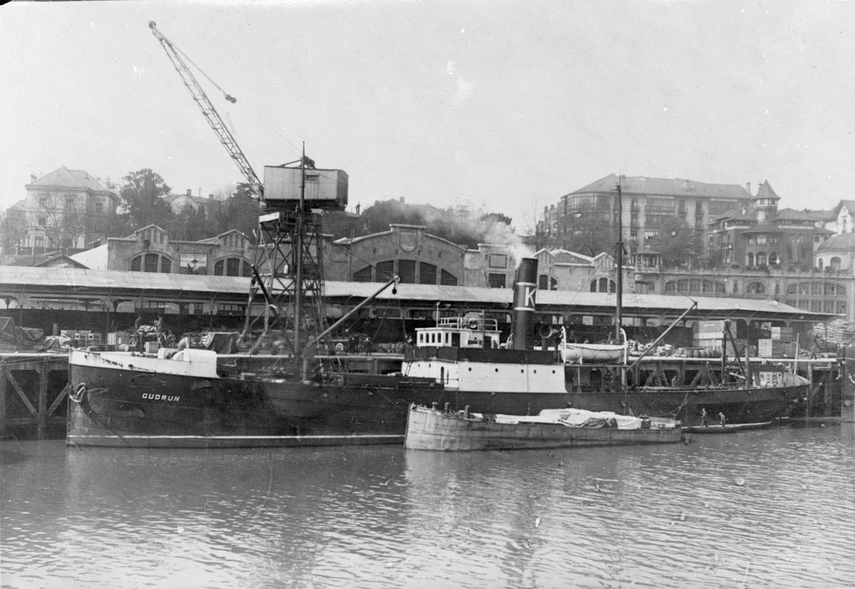 """Damskipet D/S """"Gudrun"""" ved kai i ukjent by. Det er full aktivitet på kaien og på dekk. Ved skipssiden ligger en lastebåt og en robåt.."""