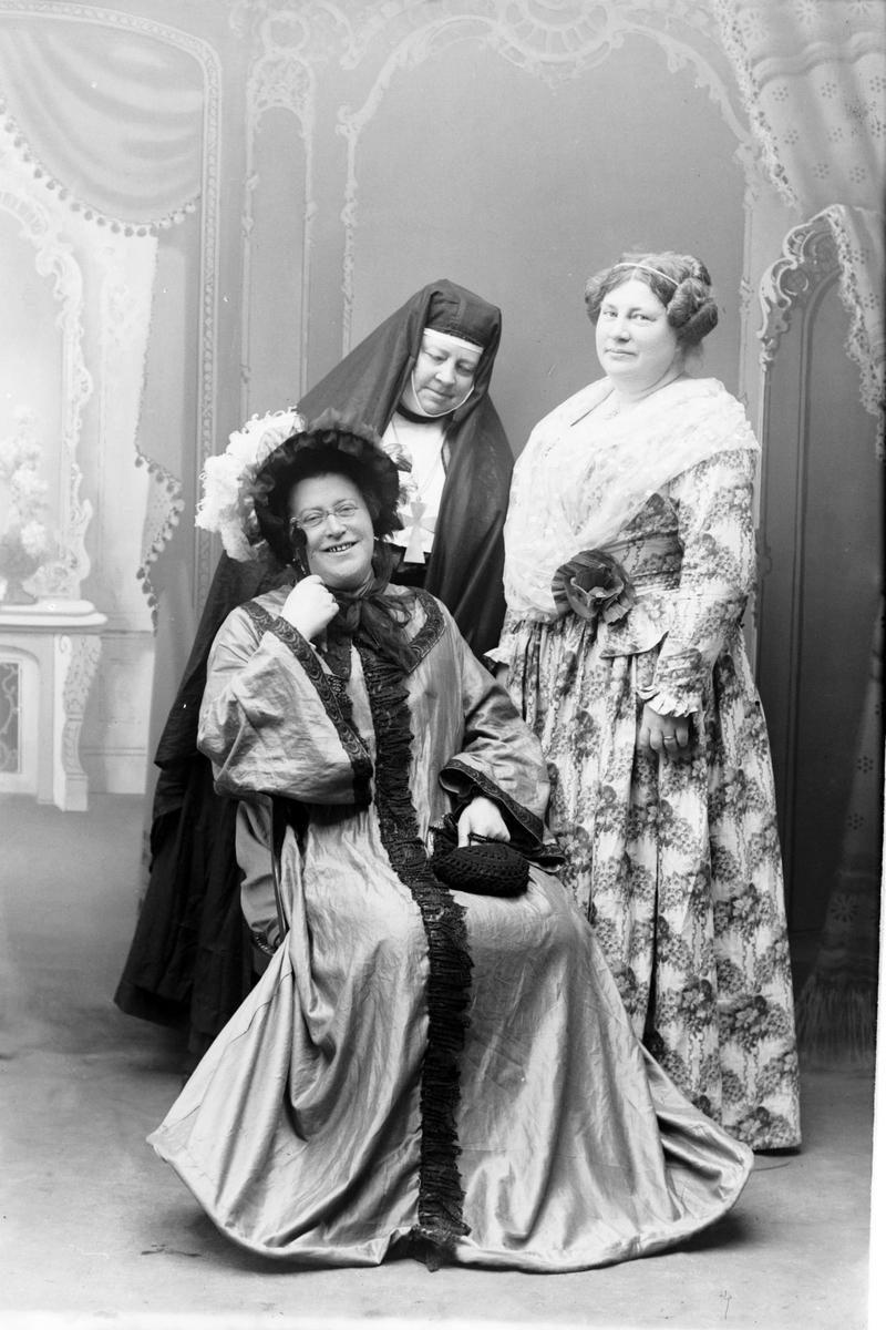 Studioportrett i helfigur av tre kvinner i kostymer.