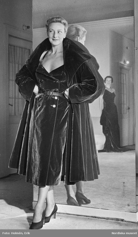 Modell i klänning och kappa i sammet, lutar sig mot spegel. Modell i långklänning i spegelbilden. Höst.
