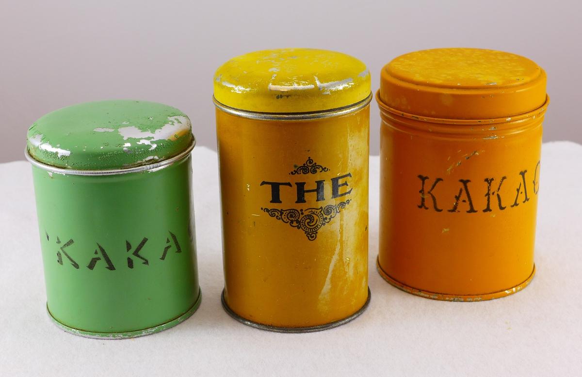 Tre metallboksar med lok til oppbevaring av te og kakao i lausvekt. Det er skrive på utsida av boksane kva som er i dei. Det er enno pulver i den eine kakaoboksen.