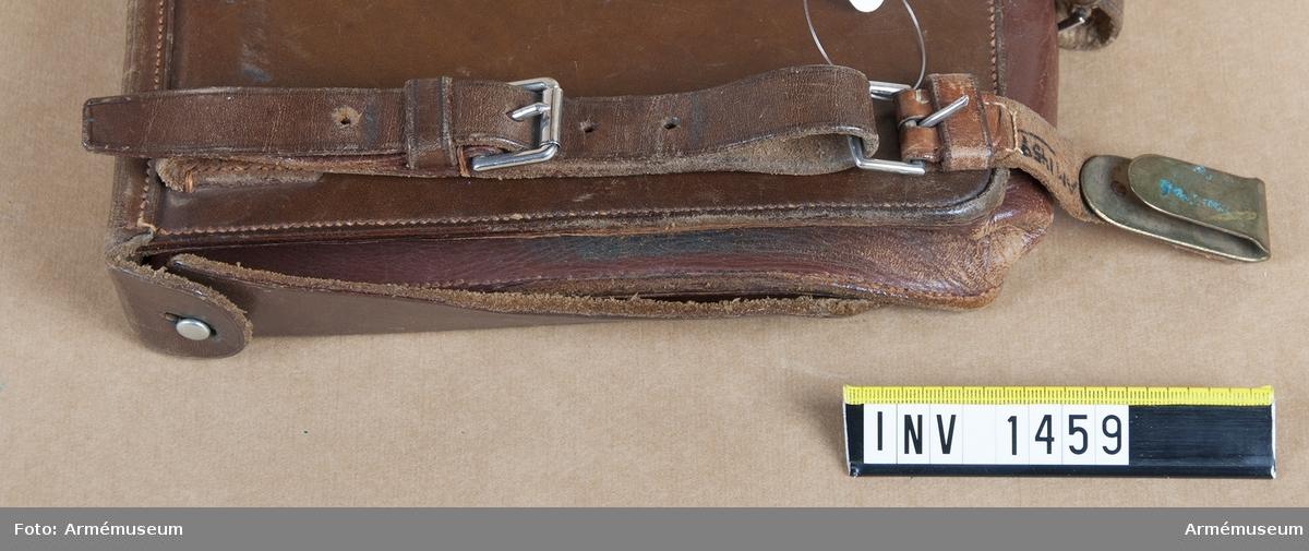 Rem till väska för anteckningsmateriel, officer. Fastträdd i väskans remmar i spännet. Upptill försedd med platt hake för fastsättning i livrem.