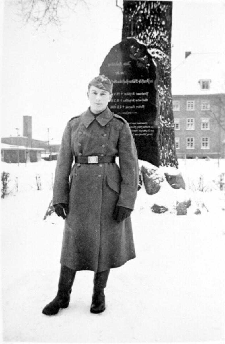 Portrett, 1 person, mann i militæruniform. Ved gravstøtte/minnesmerke.