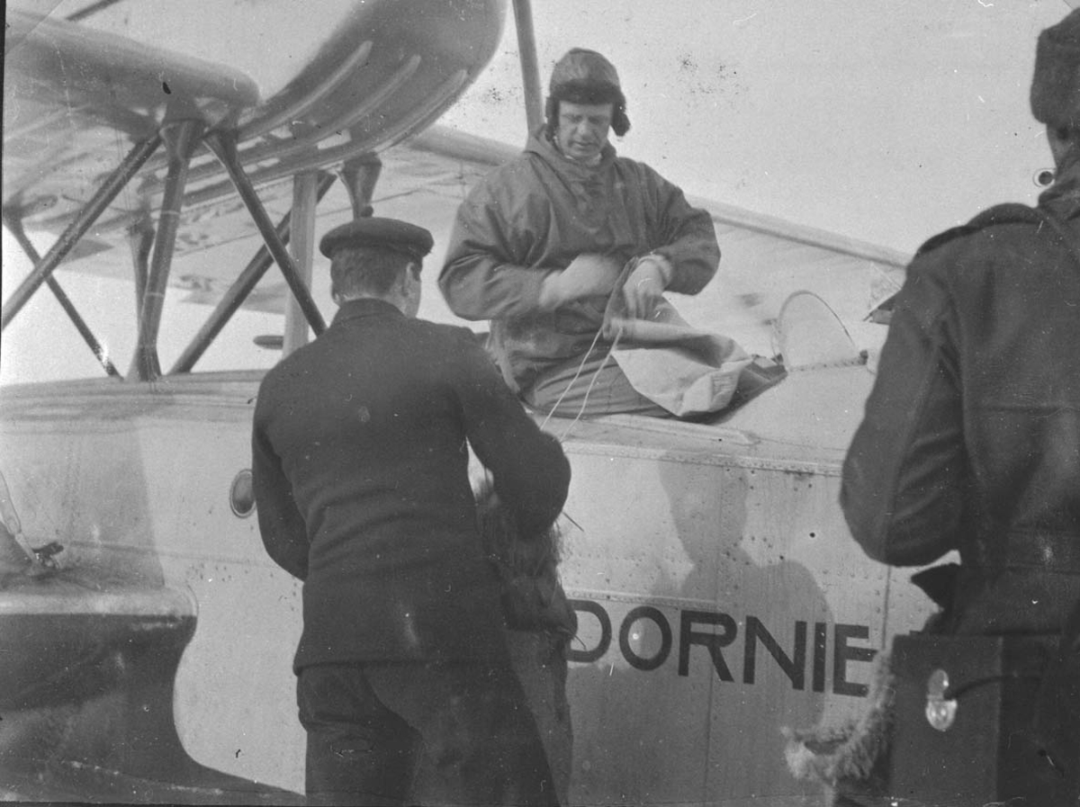 1 fly, Dornier Wal N-25 eller N-24 på isen. 3 personer ved flyet.