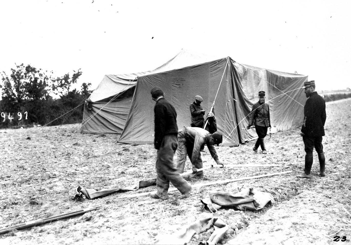 Ett telt (skvadrontelt) for militært personell. Flere personer, menn i militæruniform, i forgrunnen.
